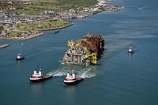 Two tugboats pull the Perdido spar from Texas shore to Alaminos canyon, where it