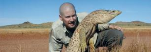 Dr Bryan Fry with a desert spotted monitor.