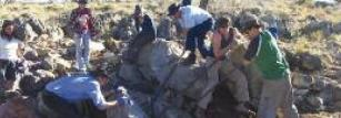 Prof Michael Archer and students shifting a block packed with fossils.