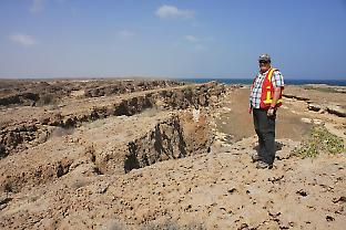 Peter Betts standing on exposed coral reef on the Farasan Islands
