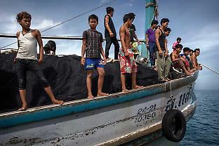 A crew of Cambodian boys and men work on a Thai fishing ship a couple hundred miles off the coast of Thailand in the South China Sea. Credit: Ian Urbina / New York Times